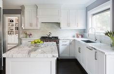 source: Jodie Rosen Design website  Fabulous kitchen features crisp white cabinets paired with white and grey marble countertops and mosaic linear backsplash framing white range hood over Wolf Range next to picture window above wide sink situated beside concealed dishwasher hidden behind paneled door.