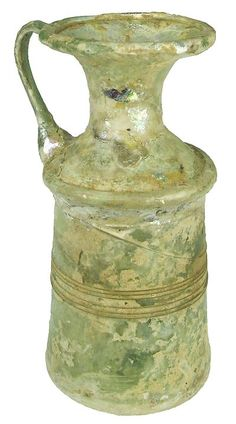 Roman glass :    Miniature light green glass pitcher, cylindrical neck, rolled rim, a single trailed handle to the shoulder and rim, some iridescence and encrustation.  50 - 100 AD