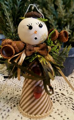Snowman decorated with acorns and trimmed in brown ribbons. Approx: 6.5 inches. Chirstmas ornament.  Price is $6.00