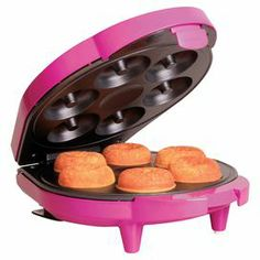 """Whip up delectable desserts with this vibrant doughnut maker, showcasing non-stick coating and space for 6 treats.  Product: Doughnut makerConstruction Material: Metal and plasticColor: MagentaFeatures:  No need for frying oilNon-stick coatingMake six doughnuts Dimensions: 4.06"""" H x 9.75"""" W x 7.88"""" DCleaning and Care: Wipe clean with a paper towel or soft cloth. For baked on batter, use vegetable oil to soften for 5 minutes and remove."""