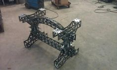 Custom designed and made wrought iron tied truss bridge table with cables. Gets glass top.  Not saying if do this exactly but something along those lines... DD wire could laser cut patterns for me..