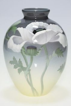 Description: Iris Glaze vase decorated by Carl Schmidt in 1904 with large, flamboyant white poppies on a shaded tan to gray background. Impressed with the Rookwood symbol, the date and shape number 902 C and incised with a W to indicate the Iris Glaze and bearing the artist's monogram. There is fine overall crazing. Beautifully composed and executed by a true master.
