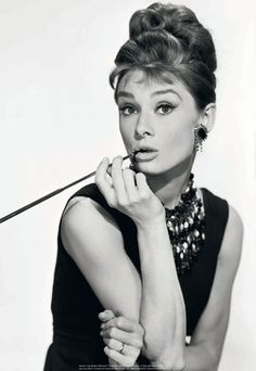 Audrey Hepburn's famous 1960s image with hair and makeup representative of the time in conjunction to her black dress with a common silhouette.