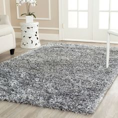 A With its hand-tufted design, this silver shag rug will add a stylish accent to a room. The rug features just enough strands of gray and blue against the silver to create a shiny look. The rug is 8 feet by 10 feet, making it ideal for any room.
