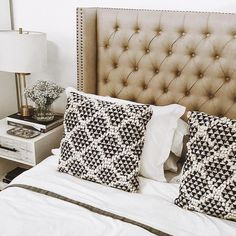A gorgeous taupe leather headboard featuring diamond tufting and brass nailhead trim, is a beautiful template for white bedding with black and white embroidered accent pillows.