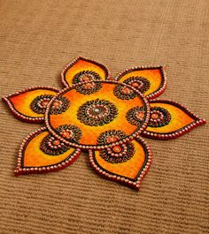 Hand Crafted Rangoli - This is a handcrafted wood & paper mache rangoli.  The rangoli is embellished with faux kundan stones and has a floral design. | indianroots.com