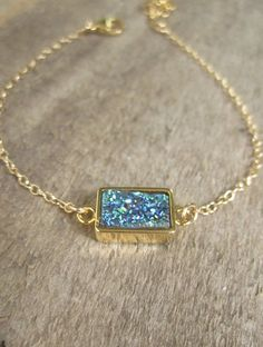 Gorgeous, midnight blue green druzy quartz gemstone is encased in 18K gold plate and linked to a delicate gold filled chain bracelet.
