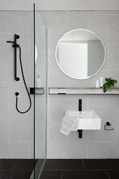 In this bathroom, white floor-to-ceiling penny tiles have been used to line the wall, while a round mirror and black accents complete create a modern look. #ModernBathroom #RoundMirror #PennyTiles #BathroomDesign #InteriorDesign