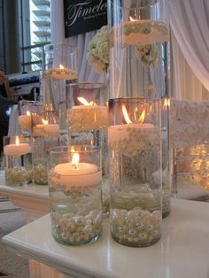 Glass cylinders filled with water and floating candles and pearls. #weddingcandlesdecorations