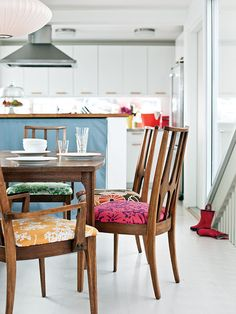 With compact cabinets and a kitchen island, this small coastal kitchen has enough room for a breakfast area. Varying vintage-inspired fabrics spice up simple dining chairs and bring color into this white kitchen area. (Photo: Thomas J. Fabric Dining Room Chairs, Woven Dining Chairs, Mismatched Dining Chairs, Kitchen Chairs, Table And Chairs, Dining Area, Chair Fabric, Chair Cushions, Chair Pads