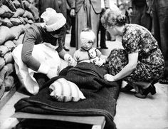 A young English girl, injured during the beginning of the Blitz, is comforted by a British nurse and a civilian. Between 7 September 1940 and 21 May 1941 there were major aerial raids (attacks in which more than 100 tons of high explosives were dropped) on 16 British cities by the German Luftwaffe.