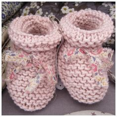 Hand knitted baby booties in pink organic cotton. They are decorated with lovely frayed nodes in Liberty Fairford  that give them their charm. $25
