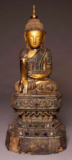 Large 18thC Burmese Shan Buddha sculpture carved from Teak lacqured and inlayed with glass fragments and gilded with gold leaf. Seated on a high altar this buddha has a very fine look and perfect poise. We purchased this sculpture last year from a collector in Kensington London along with the [13th-14thC Thai Fragmentary Ayutthaya Period Buddha]. Since then we have been doing research on the feint inscription on the lower part of the altar. Which has been translated by the Wat Sai Moon…