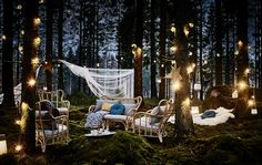 A lounge area at night in a forest wedding with rattan armchairs, lots of cushions, lighting chain and hanging lanterns
