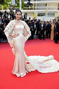 Sonam Kapoor in a Ralph & Russo silk crêpe gown in champagne, accompanied by a silk organza cocoon cape laden with hand-cut organza and feather blooms at #CANNES2016