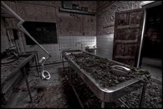 Morgue at Cambridge Military Hospital, UK.     This morgue is incredibly decayed and seems to be returning to nature, with leaves covering the autopsy table and floor. Yet there is also something of the absurd here, with a telephone left on the table as if waiting for someone to answer it.