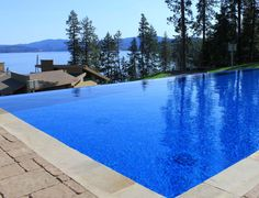 Complete perfect infinity-edge main pool with a raised, overflow infinity spa back closer the house. Jimmy Reed design and installed the Bisazza glass mosaic tiles for the exclusive home in wealthy Coer d' Alene, Idaho!