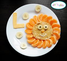 "L is for Lion! This is made with half a toasted english muffin (or bagel) with peanut butter, banana and blueberry eyes, orange nose & slivered almond mouth. The mane is made with clementine oranges, garnished with bananas, and a cheese letter L (you could also slice the rest of the banana lengthwise to make the ""L"" in two pieces instead of using cheese)."