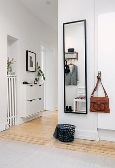 Bright and modern entryway with wooden floorboards and a mirror.