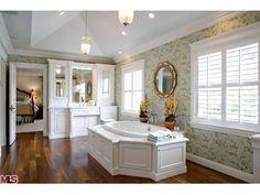 This LA bathroom has hardwood floors, an oval bathtub set in wood paneling, floral wallpaper. plantation shutters, an elaborate vanity, high ceilings, and hanging light fixtures.