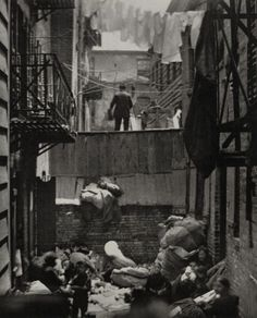 "ca. 1880-1890, Manhattan's Lower East Side — Photo by Jacob Riis. ""More than 100,000 immigrants lived in rear apartments (behind other buildings) that were wholly unfit for human habitation. In a room not thirteen feet either way slept twelve men and women, two or three in bunks set in a sort of alcove, the rest on the floor. There were also rooms where people could sleep for five cents a night, stranger next to stranger."":"
