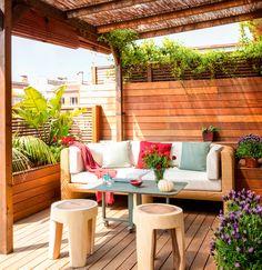 Terraza con tarima, pared de lamas de madera horizontal, sofá de fibra, taburetes inspiración tronco, plantas y pérgola de caña
