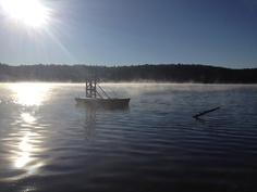 Fall morning of Little Hawk Lake bathed in mist and fog. Algonquin Highlands, Ontario, Canada.