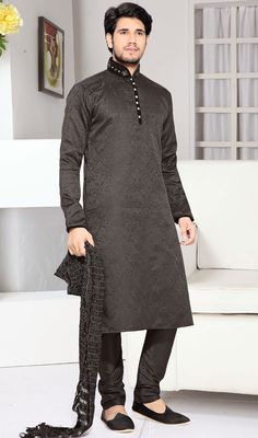 Make a distinct fashion statement with this black shade brocade and art silk kurta pyjama. The desirable moti and stones work a vital feature of this attire. brocade might vary from actual image. #Men'sShervani