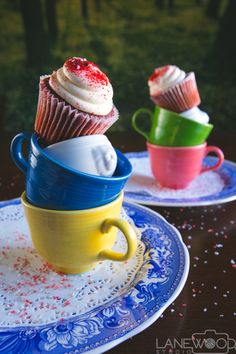Lanewood Studio Food Photography. Whimsical red velvet cupcakes with buttercream frosting and red sprinkles stacked on mini lion head bowls and blue, yellow, green, and pink Fiestaware tea cups on doilies  and Blue Spode plates.