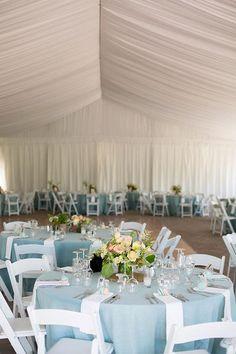 A tented reception space with blue linens | @kisakoenig | Brides.com