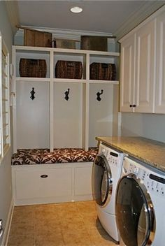 Laundry Room must haves: built-in lockers, Ikat bench cushion, drying rack, travertine floors, vintage washboards and iron, ornamental granite and oil rubbed bronze fixtures