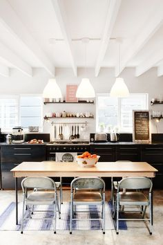 Folding chairs around the dining table in this all black kitchen