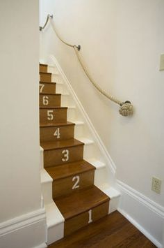 White staircase with rope handrail, numbers on steps