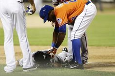 New York Mets' Eric Young Jr. (22) checks on Atlanta Braves' Tim Hudson after Hudson was hurt on a play at first base during the eighth inning of a baseball game on Wednesday, July 24, 2013, in New York. (AP Photo/Frank Franklin II)
