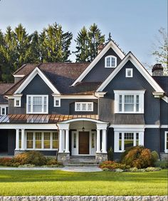 Love all the detail  lines of this homes exterior; windows, stone porch, columns, metal roof, and color.