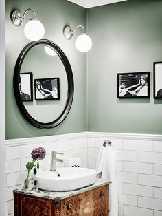 Bathroom with green walls, white subway tiles and antique vanity in a beautiful…