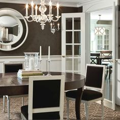 White & chocolate brown dining room design with wainscoting, brown wallpaper, round mirror, oval dining table, square back French dining chairs upholstered in brown velvet fabric and nailhead trim, acrylic chandelier and French doors.
