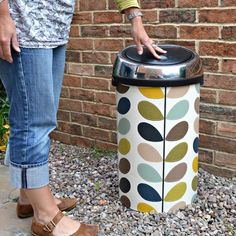 Wallpaper is not just for walls. It is a cheap and easy way of getting that designer look in your home, like this Orla Kiely bin.