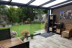 Gumax terrasoverkapping aan huis in mat antraciet zorgt voor een overdekt terras in de tuin. Met glazen schuifdeuren en een polycarbonaat dak. #glazenschuifwand #glazenschuifpui #buiten #overkapping #veranda