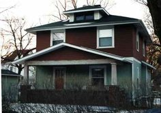 A classic American foursquare in Alton, Illinois: Wood sided with a beltcourse and a bay window.