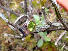 This exquisite ring features a stunning facetted Peridot with a 24-karat yellow gold setting on the front that holds the beautiful gemstone. The ring is handcrafted in 925 sterling silver and rhodium plated. Rhodium plating is used to increase the strength, durability, and bright look of silver. Rhodium (like gold) is a low tarnish metal and therefore remains bright and shiny under most environmental conditions. It enhances the beauty of silver and helps ensure the longest-lasting...