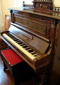 """Belíssimo piano da marca """"PERZINA"""" em madeira nobre, com entalhes na parte superior, pés torneados, três pedais. Acompanha banqueta com estofado em veludo vermelho. (Perfeito estado) Altura 132cm x 154 x 35cm."""