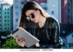 Beauty girl reading news on the tablet on a beautiful spring day outside #shutterstock #photography #microstock #urban