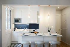 Après travaux : une cuisine blanche rénovée avec coin bar