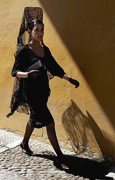 Joven ataviada con la mantilla clásica de Jueves Santo, pasea por el sevillano barrio de La Macarena. Autor Chema Moya.