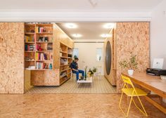 Moveable library-style shelving units slide from side to side to reveal and hide compartments that serve various functions in this Spanish apartment.