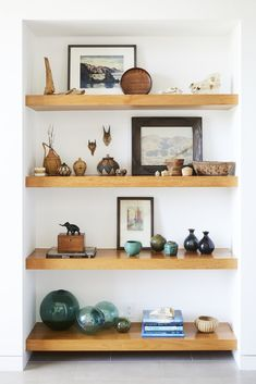 This Renovation Will Make You Rethink the Typical Look of a California Beach House - Photo 2 of 12 - Teak shelves were used in the entryway to display the owners' art collection and souvenirs from abroad.