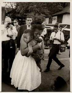 """African-American woman """"weeps as she clutches infant after white policeman rescued the child from a teargas-filled home…. Woman's hysteria, it was feared, might have touched off a new outbreak, but the rescue of four children inside the house calmed the crowd."""" Atlanta Riot, 1966."""