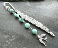 This pretty metal feather bookmark has been decorated with green glass beads, some flower shaped and some which resemble bird's eggs. A dainty bird charm hangs from the bottom. The main body of the bookmark measures It will arrive tissue wra. Organza Gift Bags, Flower Shape, Beaded Flowers, Hobbies And Crafts, Bookmarks, Turquoise Bracelet, Glass Beads, Feather, Charmed