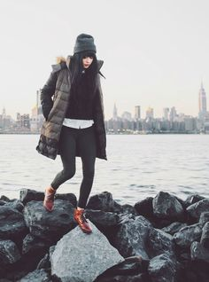 black sweater, white button down, black bottoms, parka, cognac boots